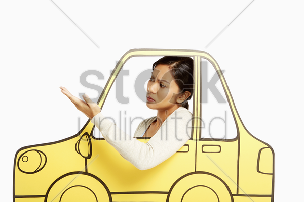 annoyed woman looking out of a cardboard car window stock photo