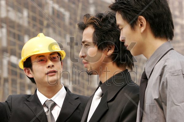 architect discussing a building plan with his client at a construction site stock photo