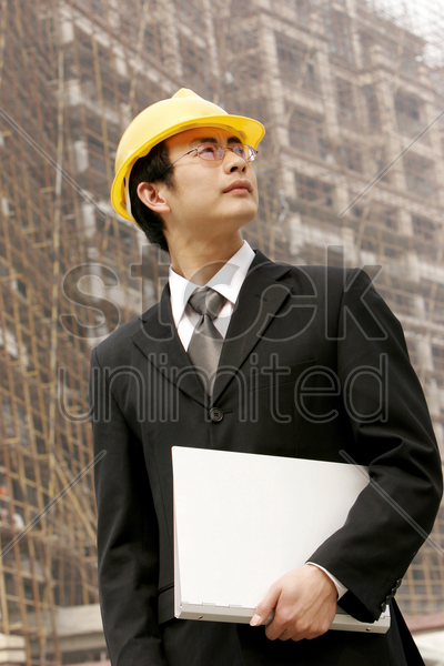 architect holding a document at a construction site stock photo