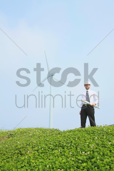 architect holding a roll of blueprint stock photo