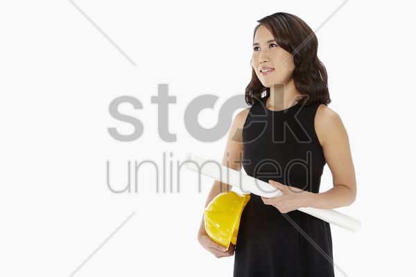 architect holding on to her construction plan and hardhat stock photo