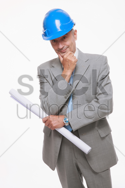 architect with blueprint touching his chin stock photo