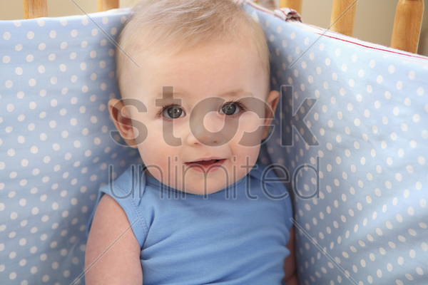baby boy sitting in crib stock photo