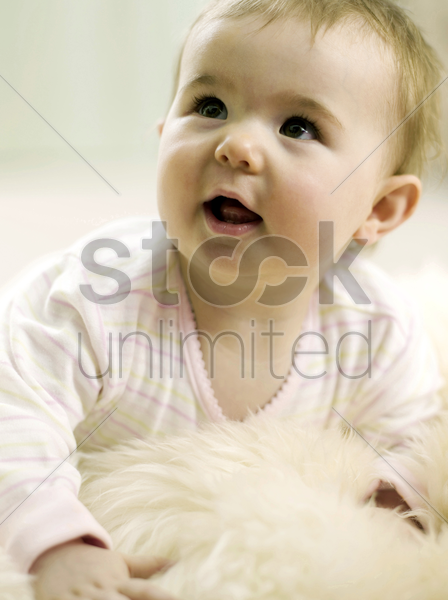 baby girl looking up while lying forward stock photo