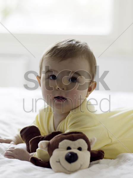 baby girl lying forward on the bed with her toys stock photo