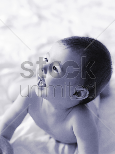 baby girl lying forward on the bed stock photo