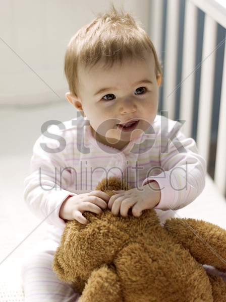 baby girl playing with her teddy bear in the crib stock photo