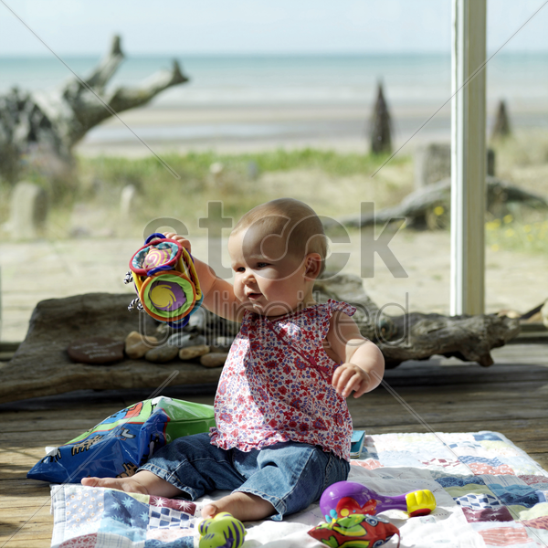 baby girl sitting on the picnic blanket playing with her toys stock photo