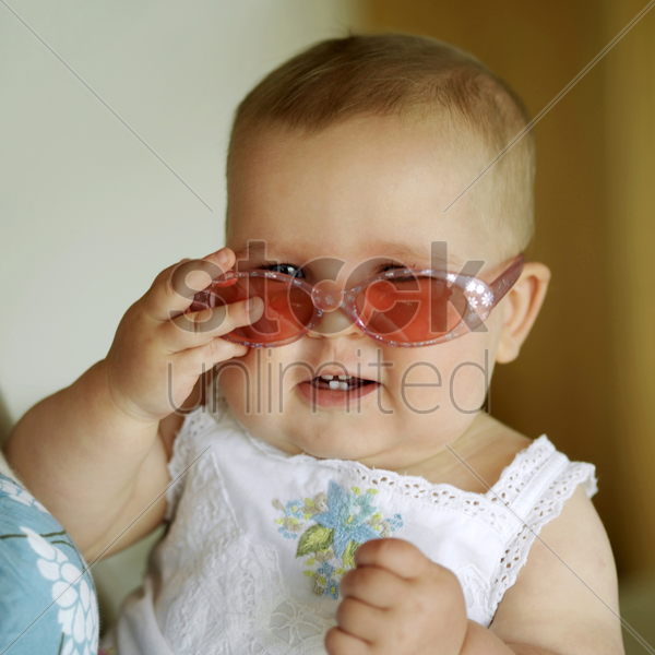 baby girl smiling while wearing sunglasses stock photo