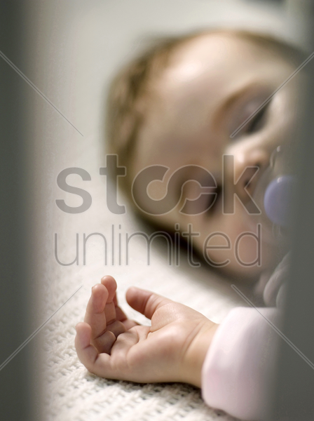 baby girl with pacifier sleeping in the crib stock photo