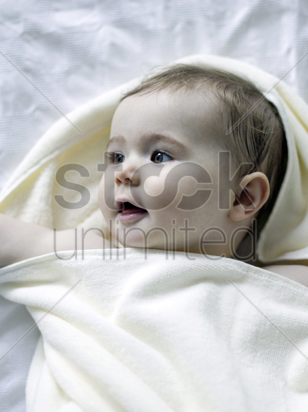 baby girl wrapped in a towel stock photo