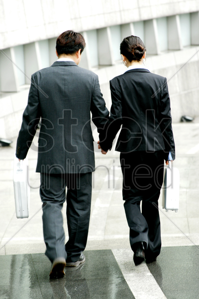 back shot of a couple in office attire holding hands stock photo