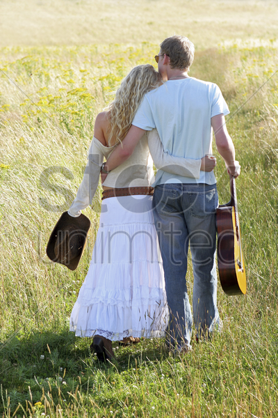 back shot of a couple walking together on the prairie stock photo