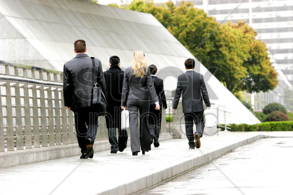 back shot of a group of sales people walking by the roadside stock photo