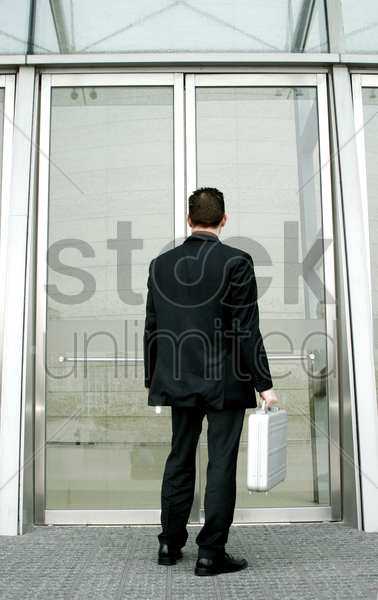 back shot of a man carrying a briefcase stock photo