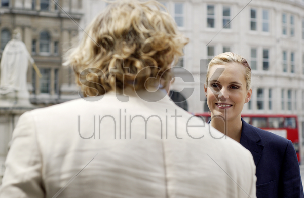 back shot of a man talking to a woman stock photo
