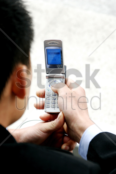 back shot of a man text messaging stock photo