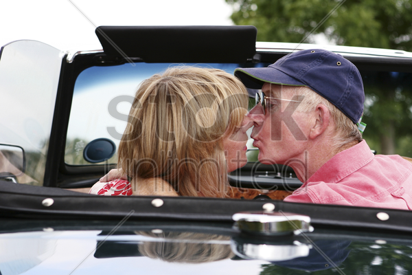 back shot of a married couple kissing in the car stock photo