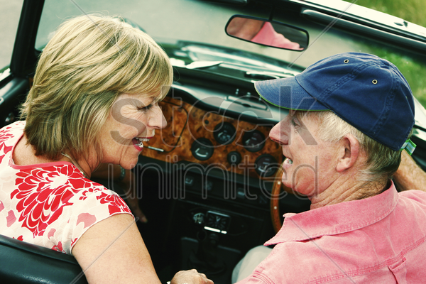back shot of a married couple sitting in their roofless car talking stock photo