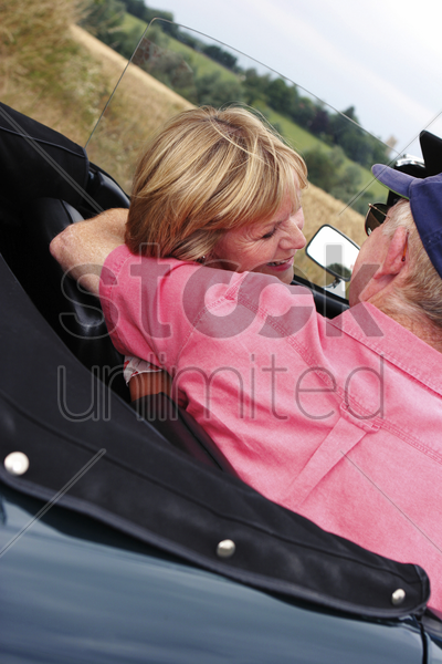 back shot of an old man placing his hand around his wife's shoulder while sitting in the car stock photo