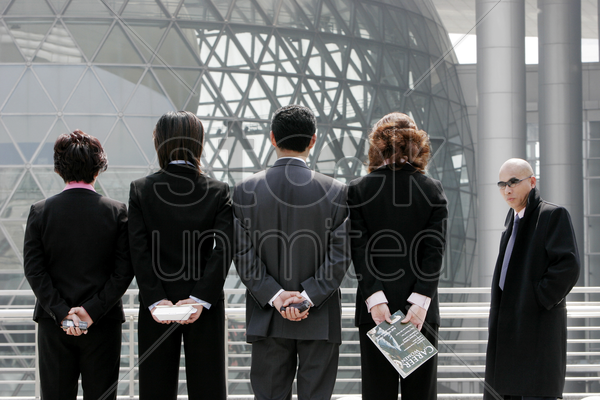 back shot of business man and women standing in a row hiding their stuff stock photo