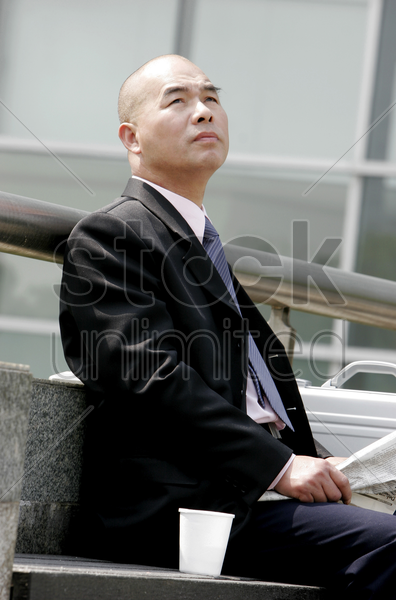 bald businessman sitting on the bench reading newspaper stock photo