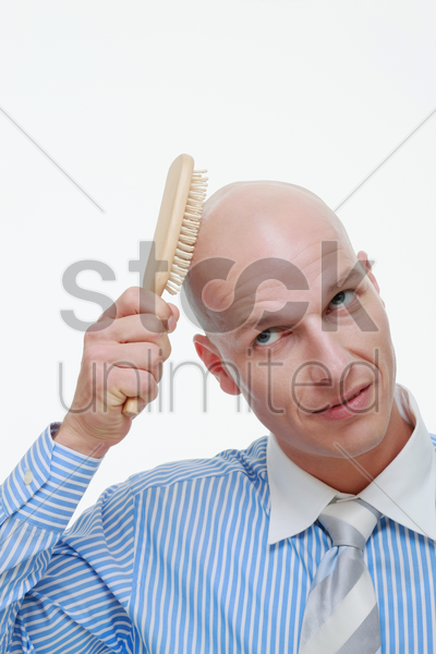 bald man combing his head stock photo