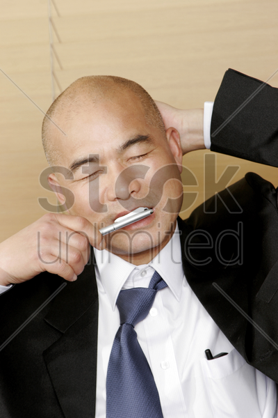 bald man in business suit brushing his teeth stock photo