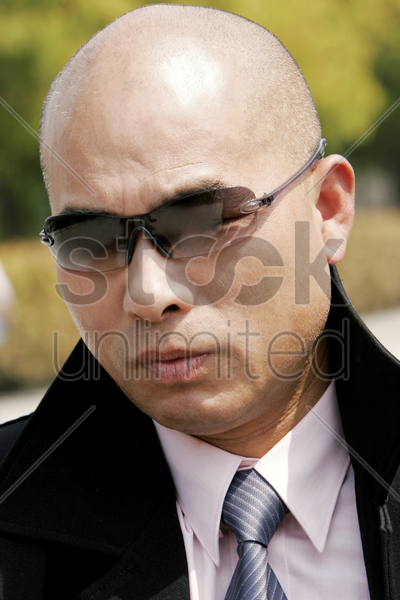 bald man in business suit looking smart with sunglass stock photo