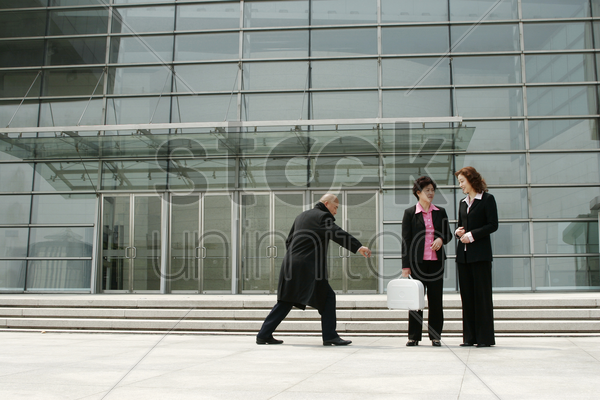bald man trying to snatch a business woman's briefcase stock photo