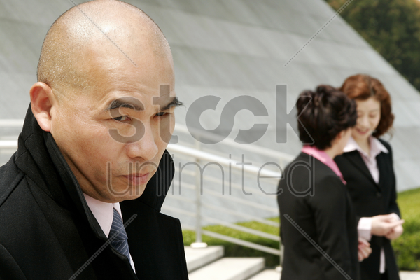 bald man with bad intention towards the two business women stock photo