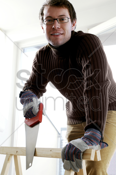 bespectacled man sawing wood on a workbench stock photo