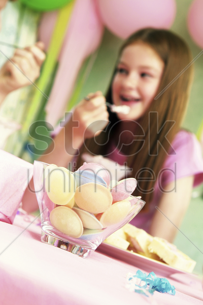 birthday girl eating ice-cream while talking stock photo