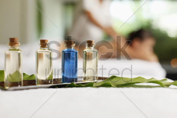 bottles of massage oil, woman receiving back massage in the background stock photo