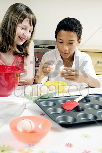 boy and girl baking cake in the kitchen stock photo