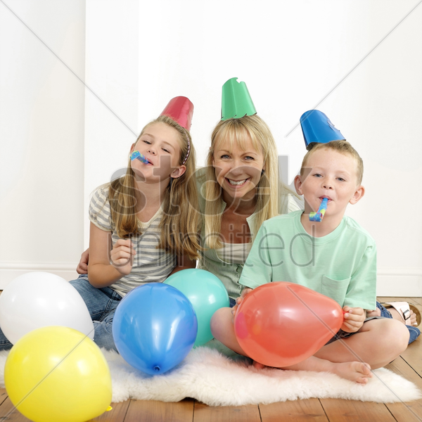 boy and girl blowing party horn blowers, woman sitting in between them stock photo