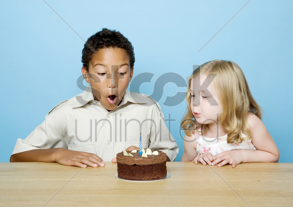 boy and girl blowing the candle on a birthday cake stock photo