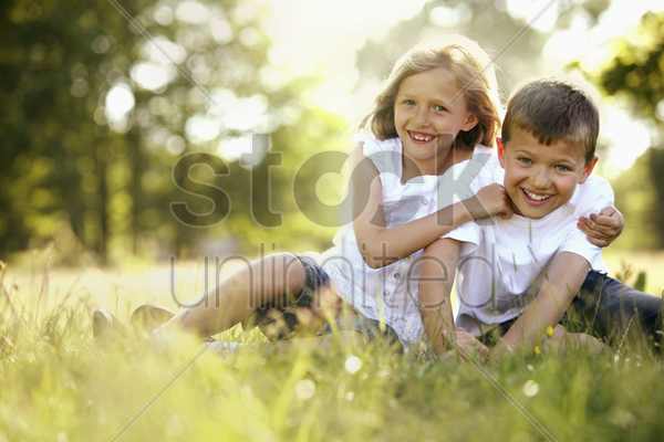 boy and girl having fun in the park stock photo