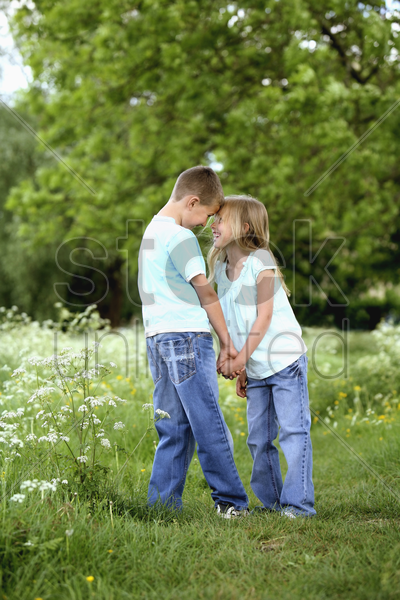 boy and girl holding hands in the park stock photo