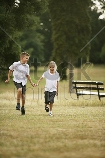 boy and girl holding hands while running in the park stock photo