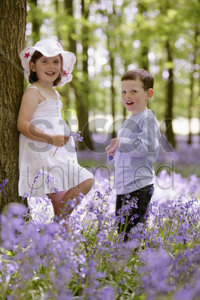 boy and girl in field of flowers stock photo