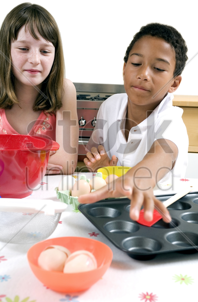boy and girl learning baking stock photo