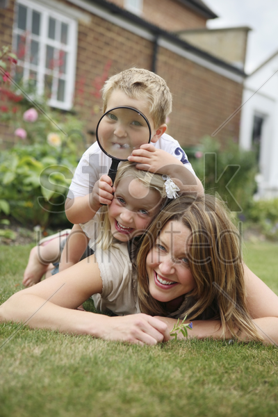 boy and girl lying forward on woman stock photo