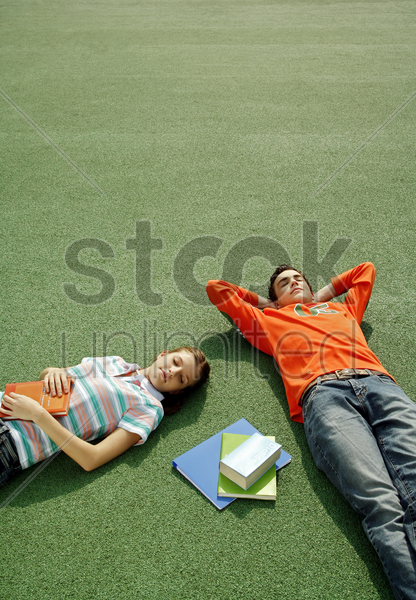 boy and girl lying on the field stock photo