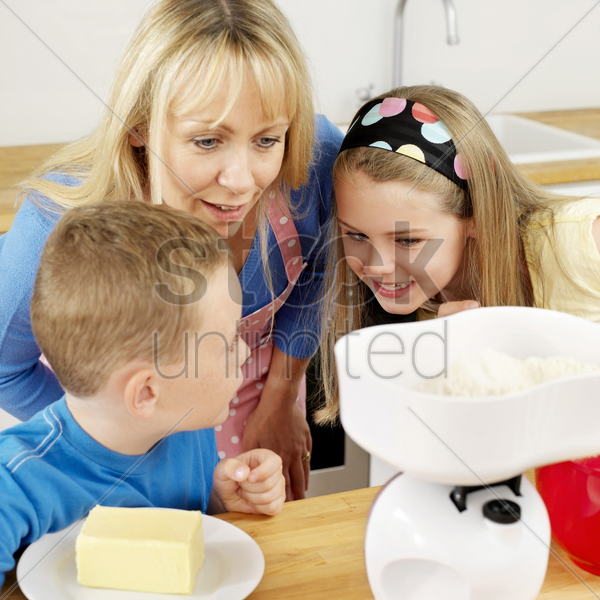 boy and girl measuring flour on weight scale, woman watching stock photo