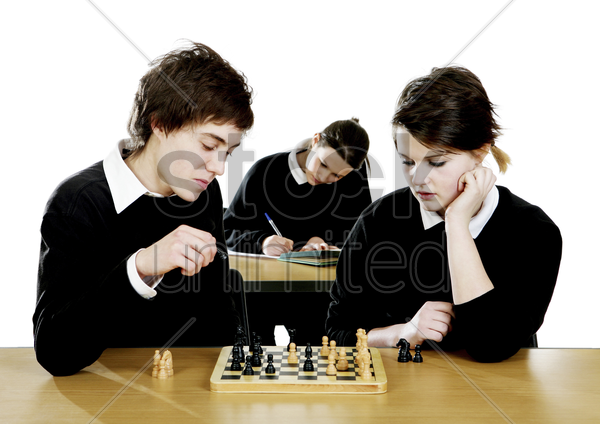 boy and girl playing chess game in the classroom stock photo