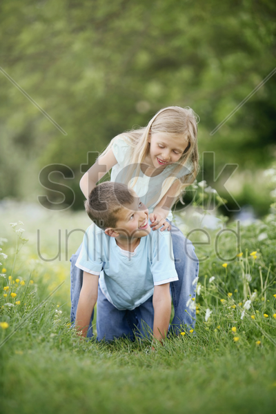 boy and girl playing in the park stock photo