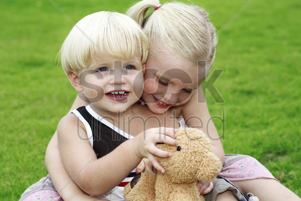 boy and girl playing teddy bear in the park stock photo