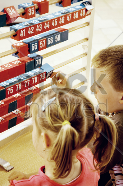 boy and girl playing with a big abacus stock photo