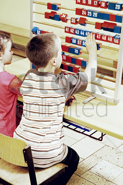 boy and girl playing with big abacus stock photo